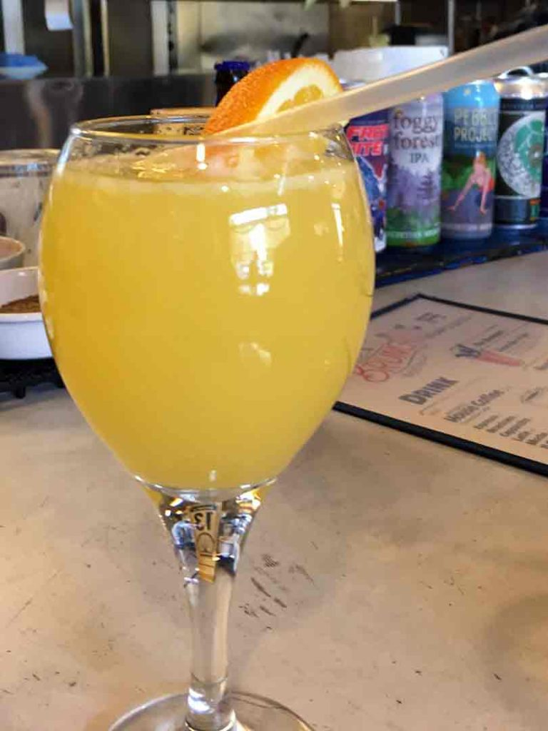 wine glass with orange beverage garnished with an orange slice