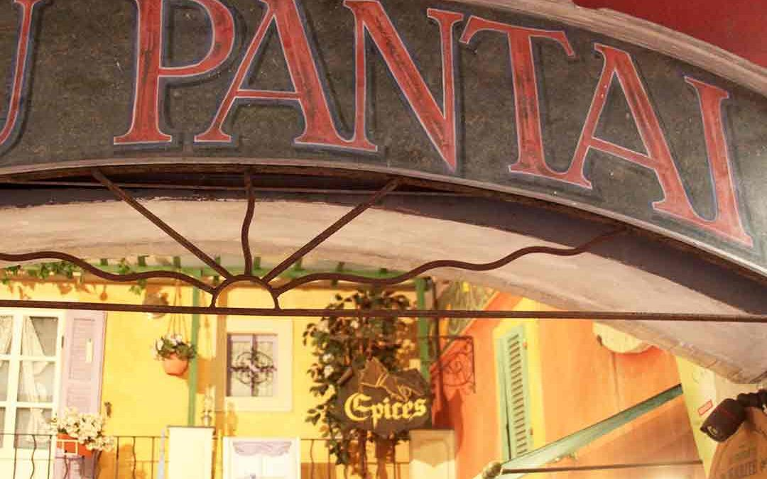 Red had lettered sign spelling out PANTAI in an arc with an orange-lit store interior below