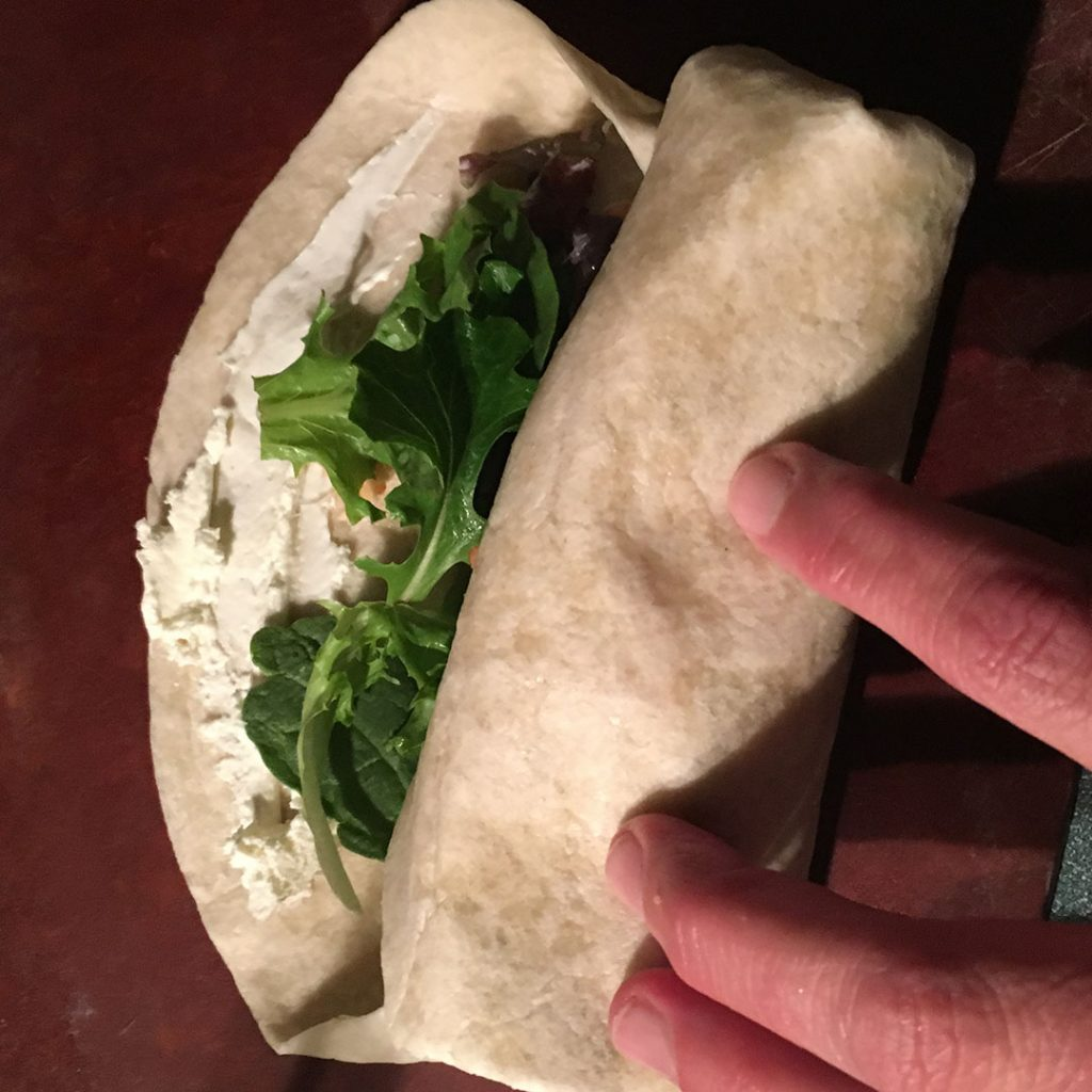 Rolling a flour tortilla with mixture